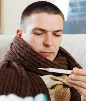 man-wrapped-in-brown-scarf-looking-at-thermometer